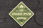 Coaster for Irish Pub. Vintage drawing for bar, pub, beer and whiskey themes. Green square or rhombus for placing a beer mug or whiskey glass over it with lettering and drawings. Vector Illustration