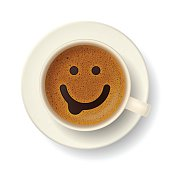 Coffee cup with funny smiling face on frothy surface. Good mood and vivacity for active day