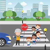 Traffic guard helping school kids crossing road by holding a stop sign.