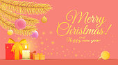 Coral and gold greeting card for Christmas and new year holidays with a copy space It shows Christmas elements such as golden branches of fir, gifts, a candle, and Christmas decoration. These are on a
