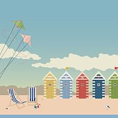 Beach scene with pretty beach huts, a seagull, two kites and a couple of deckchairs.