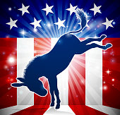 A donkey in silhouette kicking with an American flag in the background democrat political mascot