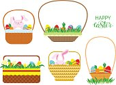Easter baskets with Easter eggs, carrots and bunnies isolated on white background.