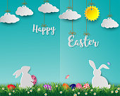 Easter eggs with white rabbits on green grass,cute paper art on soft blue background for happy holiday,vector illustration