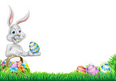 An Easter bunny rabbit with basket of Easter eggs on an egg hunt pointing with space for a message design