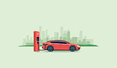 Flat vector illustration of a red electric car charging at the charger station on the street with green city skyline in the background. Electromobility e-motion concept.