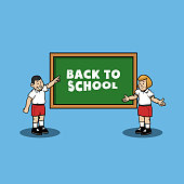 School boy and girl give back to school greeting on chalk board.