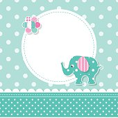 illustration of a green baby elephant with a pink ear, colorful flower, round label and ribbon on green polka dot pattern background