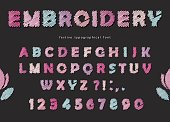 Embroidery font design. Cute ABC letters and numbers in pastel colors on the black background. Vector
