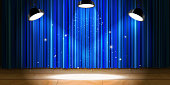 Bright empty beige wooden stage with blue drape and bright light