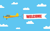 Flying advertising banner, pulled out by light aircraft with the inscription 'WELCOME' - stock vector.