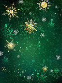 gold jewelry snowflakes on green textural background