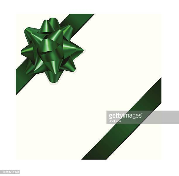 Green gift bow in front of a white background