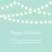 Greeting card design with Happy Holidays, Merry Christmas and Happy New Year wishes. Mint green background and fairy lights.