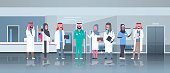 group of arabic doctors team treatment communication concept arab medical hospital mix race workers standing together modern clinic hall interior full length horizontal vector illustration