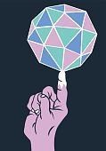 A hand balancing a colorful geodesic dome on one finger.