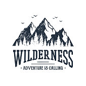 Hand drawn inspirational label with mountains and pine trees textured vector illustrations and 'Wilderness. Adventure is calling' lettering.