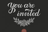 Hand drawn lettering - You are invited. Elegant modern handwritten calligraphy. Vector Ink illustration. Typography poster on dark background. For cards, invitations, prints etc