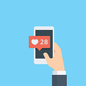 Hand giving like rating on social media with smartphone