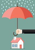 Hand holding an umbrella protecting house. Business concept
