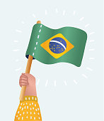 Vector cartoon illustration of human hand holding and raising the national flag of Brazil on white background.