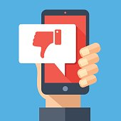 Hand holding smartphone with dislike message, dislike button. Thumbs down icon. Social networking, social media usage on mobile device. Concept for website, web banner. Flat design vector illustration