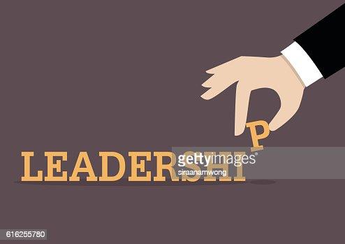 Hand inserts the last alphabet into leadership word : Arte vetorial