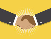 Two hands make a handshake on a yellow background and fancy the beginning of cooperation and partnerships