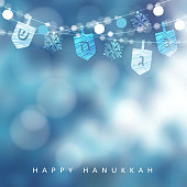 Hanukkah blue greeting card, invitation with string of lights, dreidels and snowflakes, party decoration. Modern festive blurred vector illustration background for Jewish Festival of light holiday.