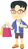 Happy asian boy holding shopping bags and giving thumb up. Little smiling boy with shopping bags. Vector sketch cartoon illustration isolated on white background.