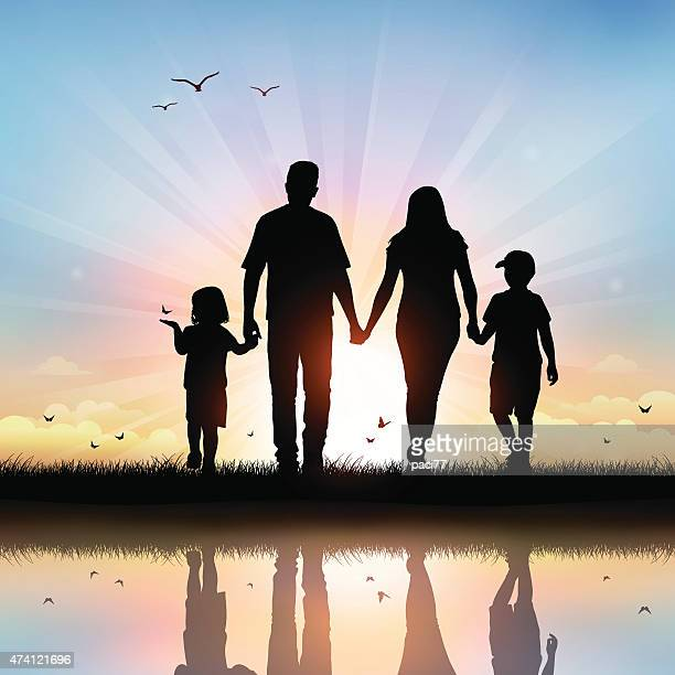 Happy Family with children walking at sunset time