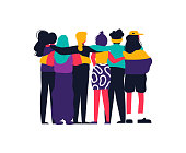 Diverse women friend group hugging together for feminist concept or womens right event. Modern young woman dressed in trendy urban fashion. Female team hug on isolated background with copy space.