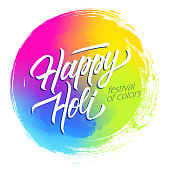 Happy Holi Indian spring festival of colors circle brush stroke colorful background with handwritten holiday greetings inscription. Vector illustration.