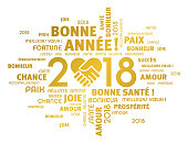 Gold greeting words in French around New Year 2018 date, composed with a handshake heart symbol, isolated on white