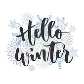 Hello winter black hand written inscription with blue snowflakes on white background