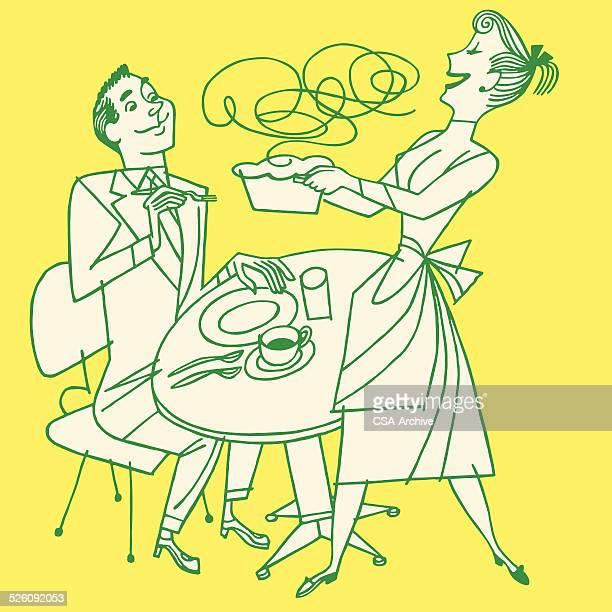 Femme à l'aide de son mari apportant le dîner