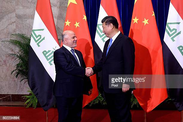 Iraqi Prime Minister Haider alAbadi shakes hands with Chinese President Xi Jinping before their meeting at the Great Hall of the People on December...