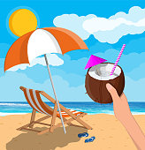 Coconut with cold drink in hand. Landscape of wooden chaise lounge, umbrella, flip flops on beach. Sun with reflection in water and clouds. Day in tropical place. Vector illustration in flat style