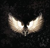glowing angel wings , decorated with a pattern on a dark textural background.