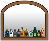 A row of liquor bottles on a shelf in front of a mirror with room for copy