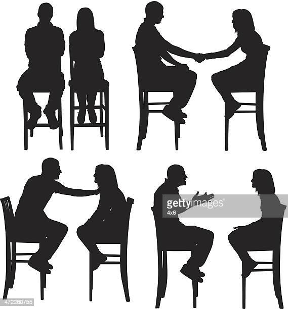 Man and woman sitting on tall chairs