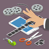 Mobile video editor flat vector isometric concept. Man's hand scotch-tapes a film tape on the smartphone surrounded by some equipment.