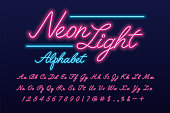 Glowing pink and blue neon light script alphabet