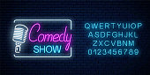 Neon sign of comedy show with retro microphone symbol with alphabet on a brick wall background. Humor monolog stand up glowing signboard. Vector illustration.
