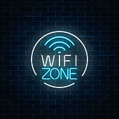 Neon sign of free wifi zone in circle frame on dark brick wall background. Wireless connection free access in cafe, night club or bar. Vector illustration.