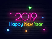 Neon text 2019 Happy New year on brick wall background decorated with colorful stars.
