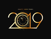 New Year celebration concept, golden text 2019 with glittering effect watch on black background.