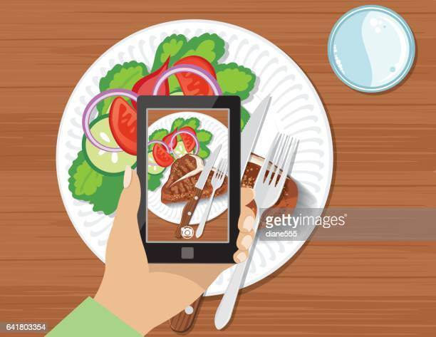 Overhead Angle Of A Person Using A Smart Phone to Take Food Photos
