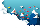 Paper airplanes flying from clouds to red flag on the peak of mountain and blue sky.Paper art style of business teamwork creative idea concept.Vector illustration