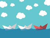 Red paper boat leading white ones sailing in sea on blue sky background. Leadership, success, teamwork and management concept. EPS 10 vector illustration, transparency used